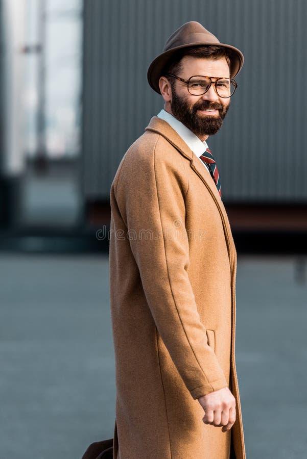 uomo d'affari barbuto felice nella condizione di vetro fotografia stock