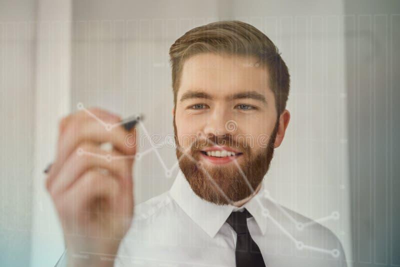 Uomo d'affari barbuto sorridente che lavora con lo schermo futuristico ed i diagrammi di disegno fotografia stock