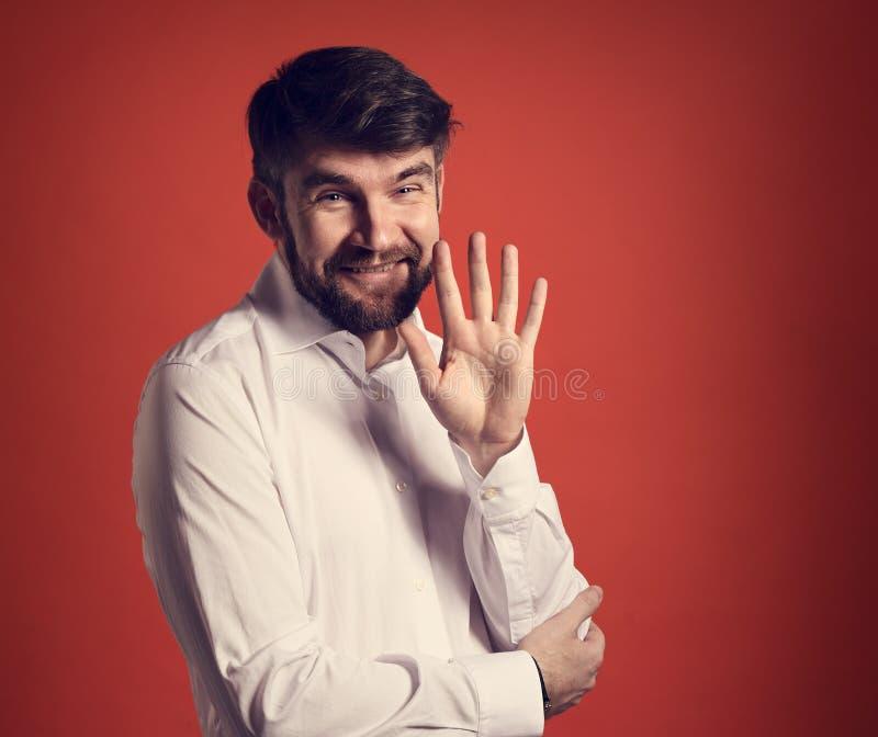Uomo d'affari barbuto sorridente felice che ondeggia la mano e che dice i hel fotografia stock