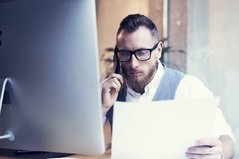 Uomo d'affari barbuto Working Workplace Report del primo piano Uomo che usando il partner di riunione di chiamata di Smartphone G fotografia stock