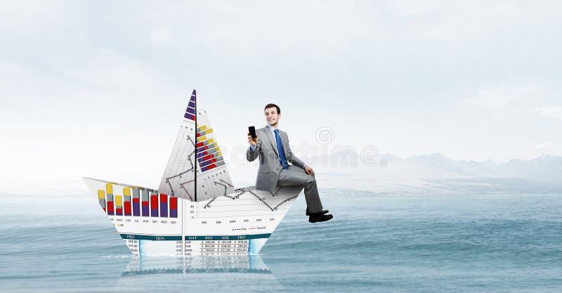 Uomo d'affari in barca fatta di carta immagini stock