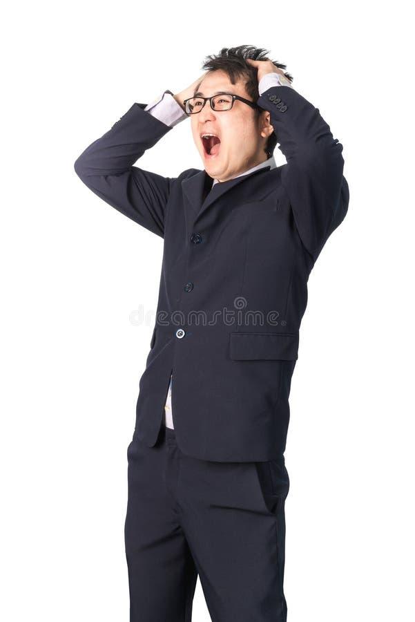 Uomo d'affari bello asiatico che tiene la sua testa che aggrotta le sopracciglia con la preoccupazione fotografia stock