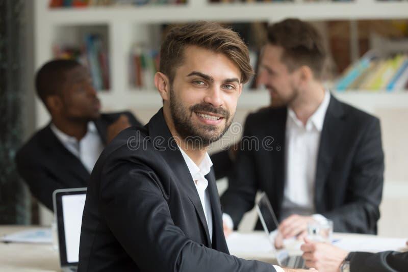 Uomo d'affari bello attraente che esamina macchina fotografica e sorridere immagini stock