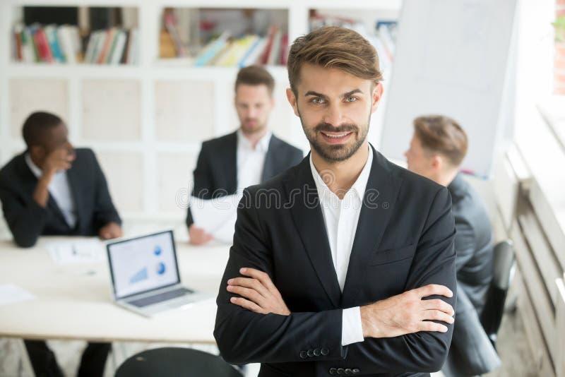Uomo d'affari bello attraente che esamina macchina fotografica e sorridere immagine stock libera da diritti