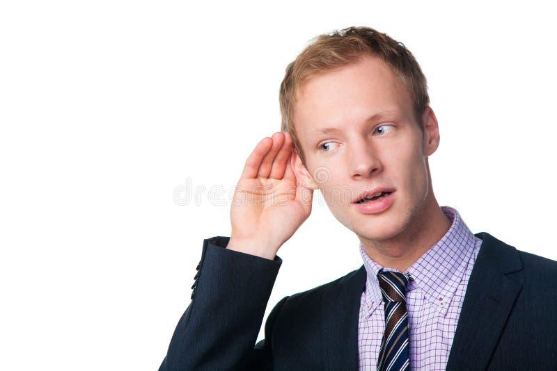Uomo d'affari bello che ascolta qualcosa fotografia stock libera da diritti