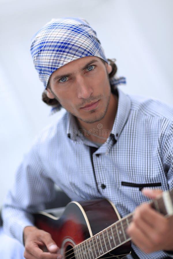 Uomo d'affari bello che gioca la chitarra in ufficio immagine stock libera da diritti