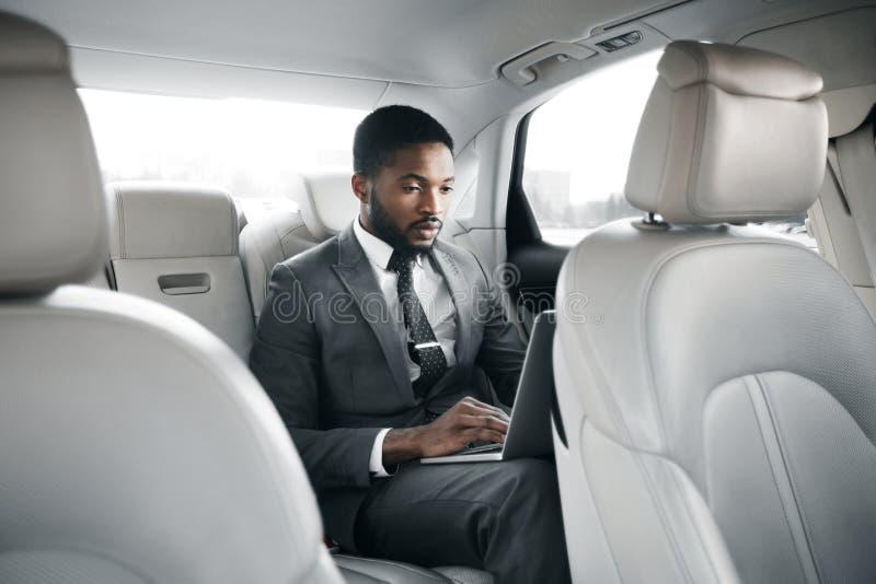 Uomo d'affari bello che lavora al computer portatile in automobile immagine stock