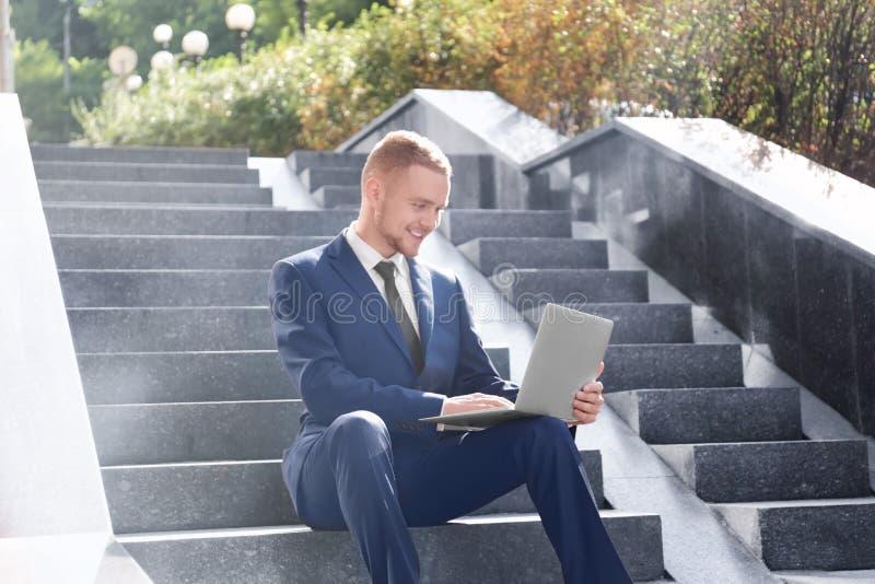 Uomo d'affari bello che lavora con il computer portatile mentre sedendosi sulle scale all'aperto fotografie stock
