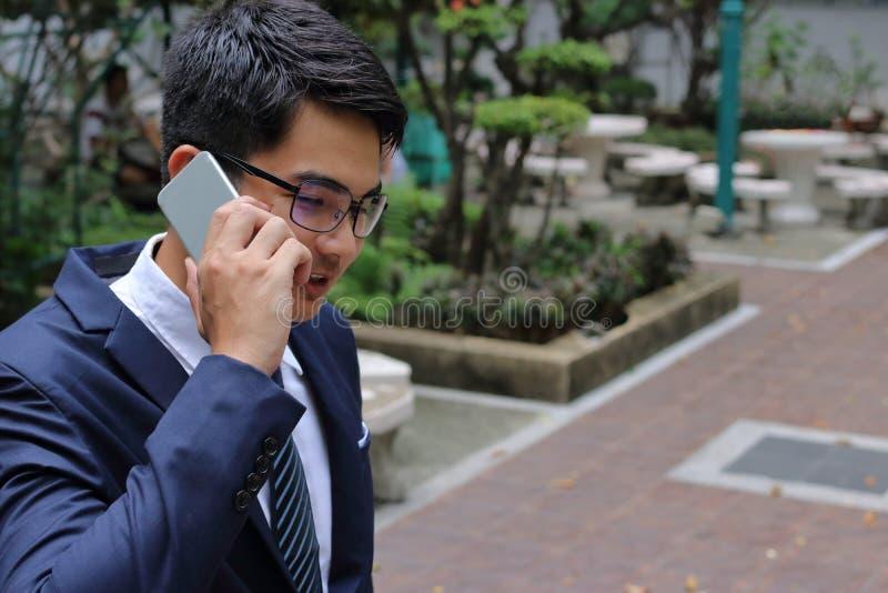 Uomo d'affari bello che parla sul suo telefono cellulare nel parco della città immagini stock