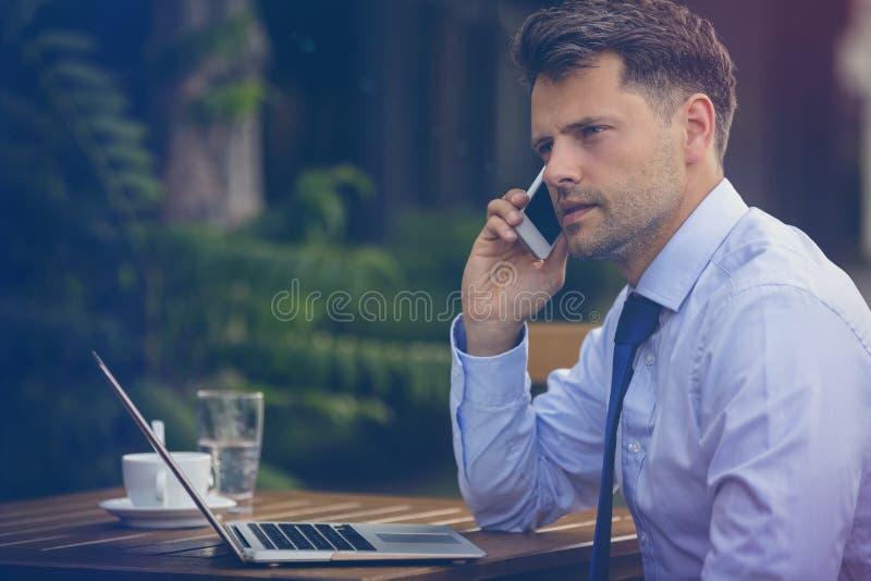Uomo d'affari bello che parla sul telefono cellulare mentre per mezzo del computer portatile immagine stock libera da diritti