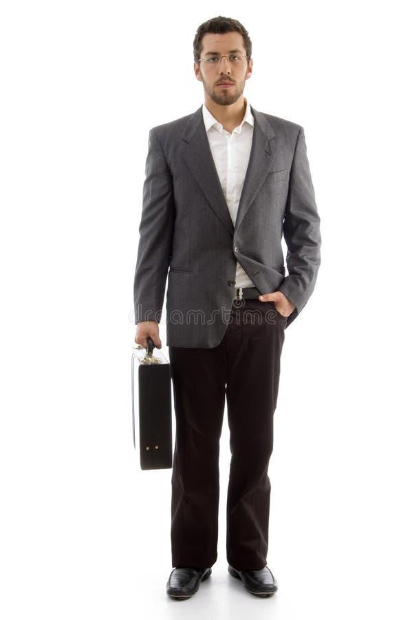 Uomo d'affari bello che si leva in piedi con il suo sacchetto dell'ufficio immagine stock