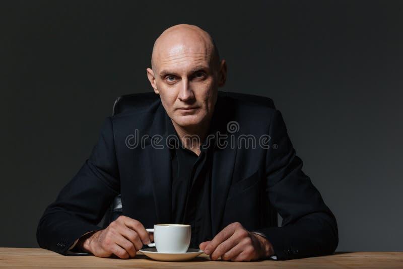Uomo d'affari bello che si siede alla tavola ed al caffè bevente fotografia stock