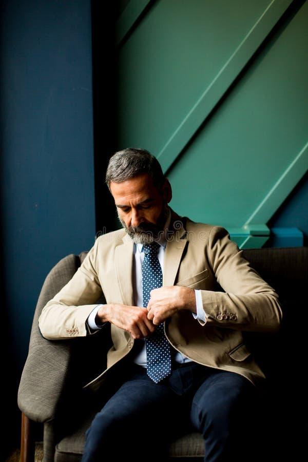 Uomo d'affari bello che si siede nell'ingresso immagini stock