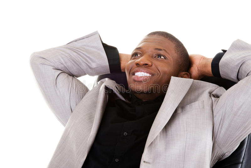 Uomo d'affari bello che si siede su un sorridere della sedia. fotografia stock