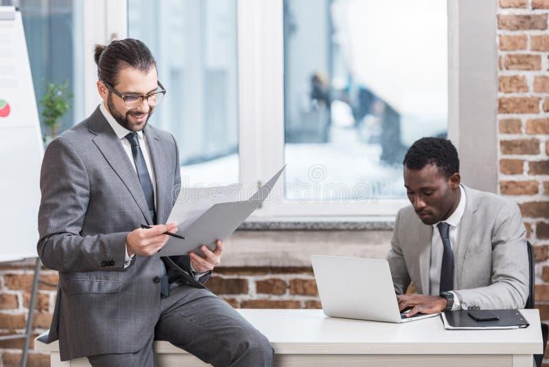 uomo d'affari bello che si siede sulla tavola e che legge documento mentre partner afroamericano che scrive sulla tastiera del co immagini stock