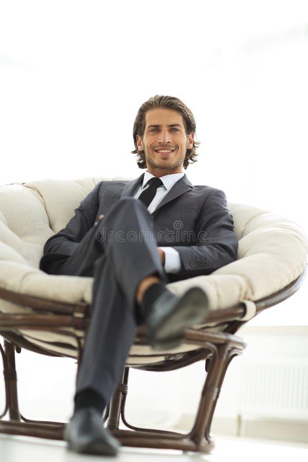 Uomo d'affari bello che si siede in una grande poltrona accogliente fotografia stock