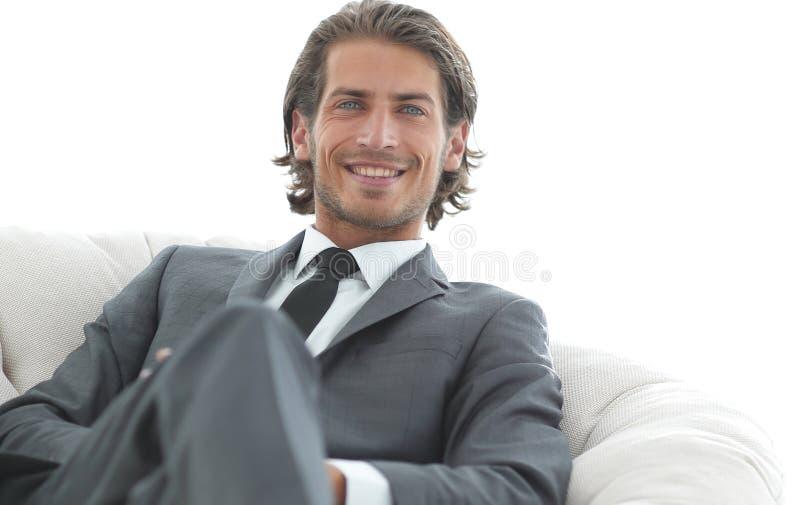 Uomo d'affari bello che si siede in una grande poltrona accogliente fotografia stock libera da diritti