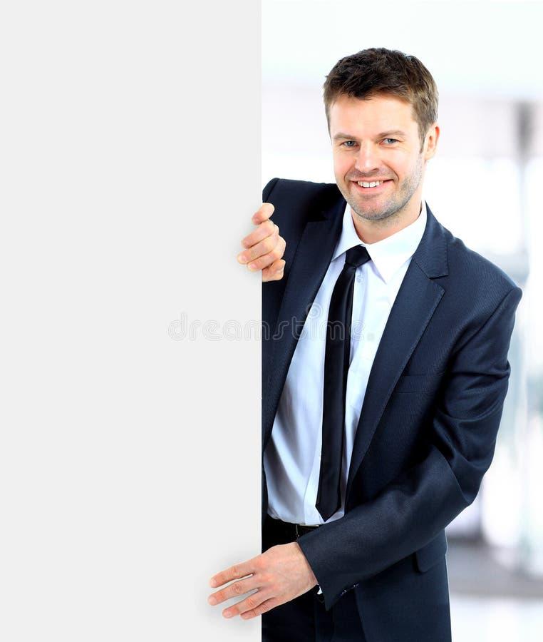 Uomo d'affari bello che tiene un segno in bianco fotografie stock