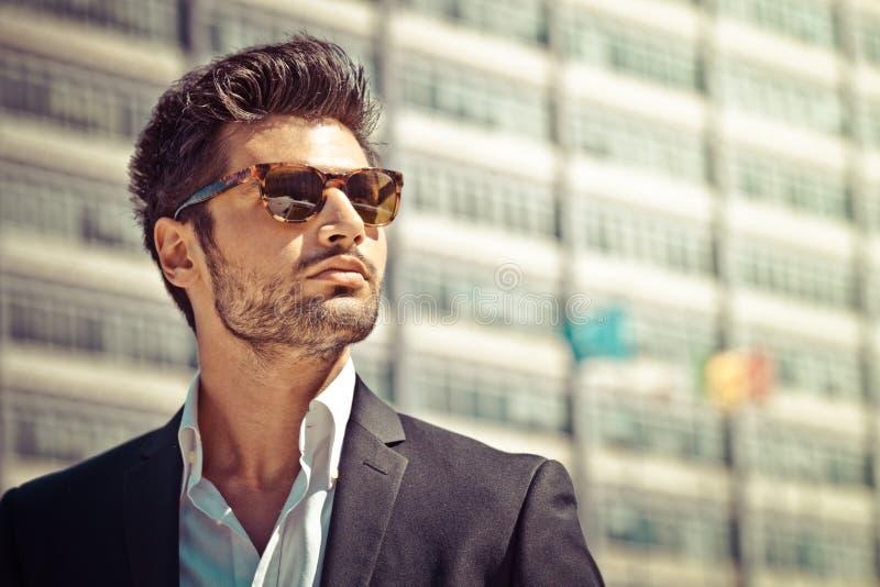 Uomo d'affari bello con gli occhiali da sole immagine stock