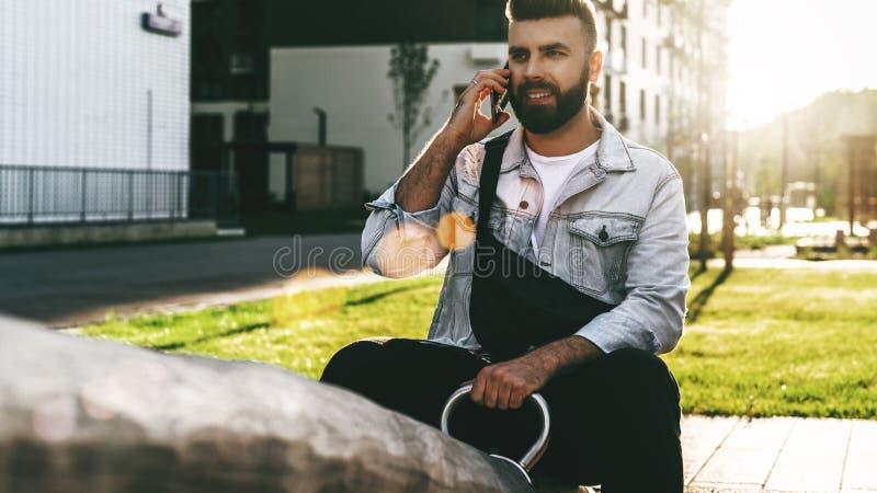 Uomo d'affari bello dei pantaloni a vita bassa con la barba, in rivestimento del denim e seduta e chiamate d'avanguardia di vetro fotografia stock libera da diritti