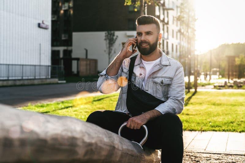 Uomo d'affari bello dei pantaloni a vita bassa con la barba, in rivestimento del denim e seduta e chiamate d'avanguardia di vetro fotografia stock