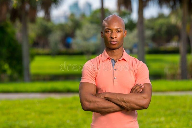 Uomo d'affari bello del ritratto giovane che posa all'aperto in una camicia di polo rosa fotografia stock