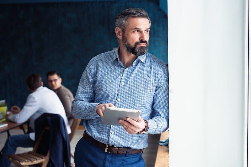 Uomo d'affari bello di medio evo con la compressa digitale nell'ufficio di modren fotografia stock