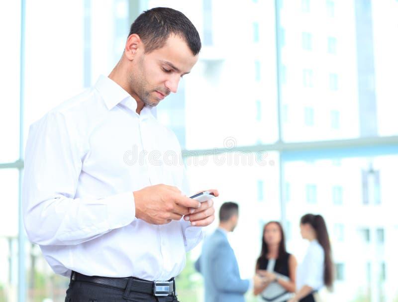 Uomo d'affari bello facendo uso di uno smartphone fotografia stock
