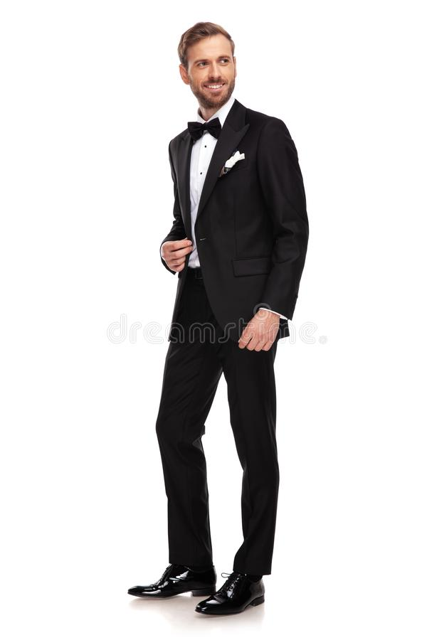 Uomo d'affari bello negli sguardi neri del vestito da parteggiare mentre stando fotografia stock libera da diritti