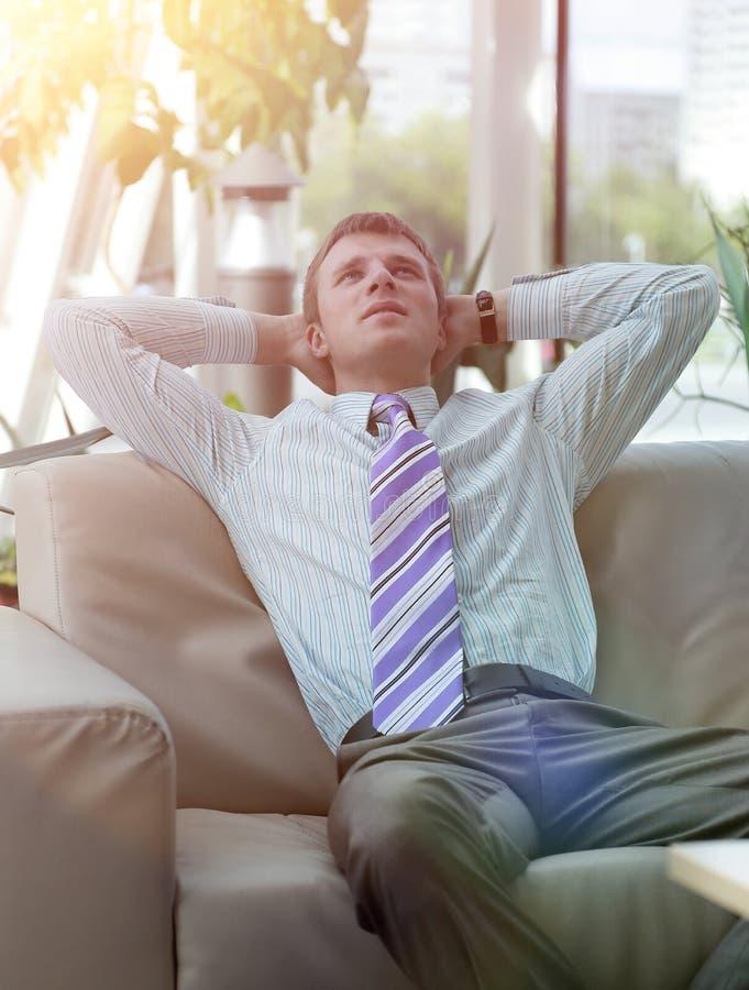 Uomo d'affari bello serio che si rilassa nell'ingresso fotografia stock