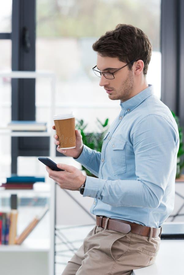 uomo d'affari bello sicuro con caffè facendo uso dello smartphone immagine stock