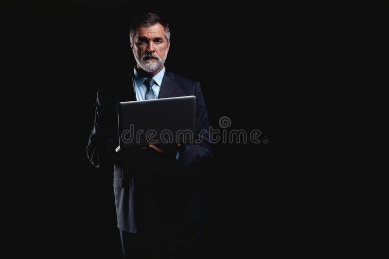 Uomo d'affari bello sorridente che lavora con il computer portatile Isolato sopra priorità bassa nera immagini stock libere da diritti