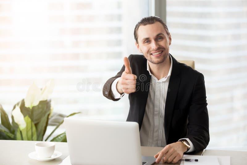 Uomo d'affari bello sorridente felice che mostra i pollici su fotografie stock libere da diritti
