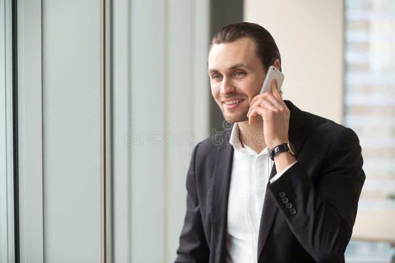 Uomo d'affari bello sorridente in vestito che parla sul cellulare immagini stock libere da diritti
