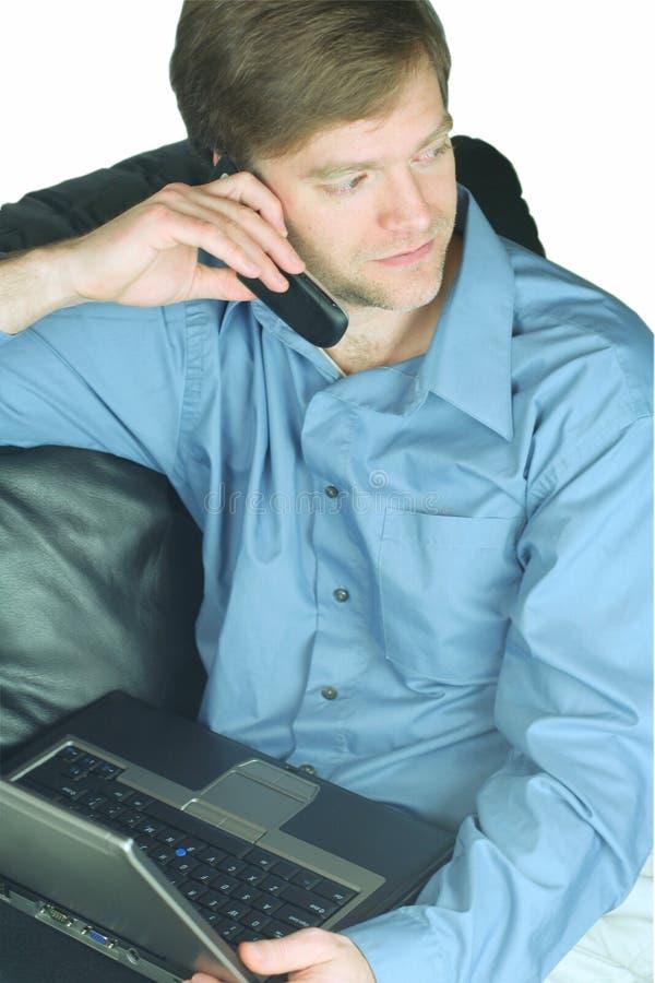 Uomo d'affari bello sul cellulare e sul computer portatile immagine stock libera da diritti