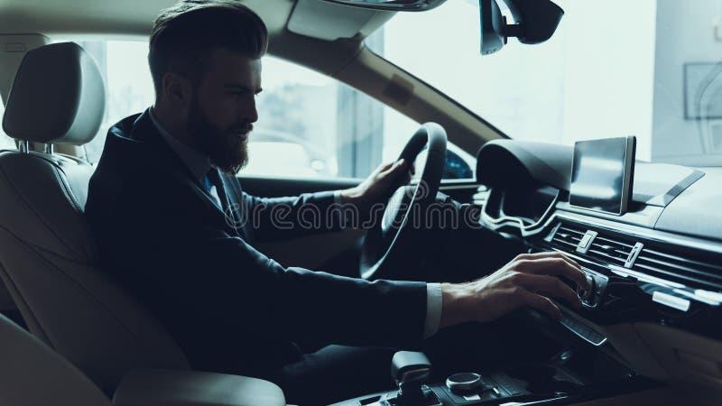 Uomo d'affari bello Turning Audio Button in automobile immagine stock libera da diritti