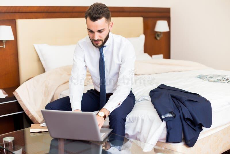 Uomo d'affari bello Using Laptop nella camera di albergo immagine stock libera da diritti