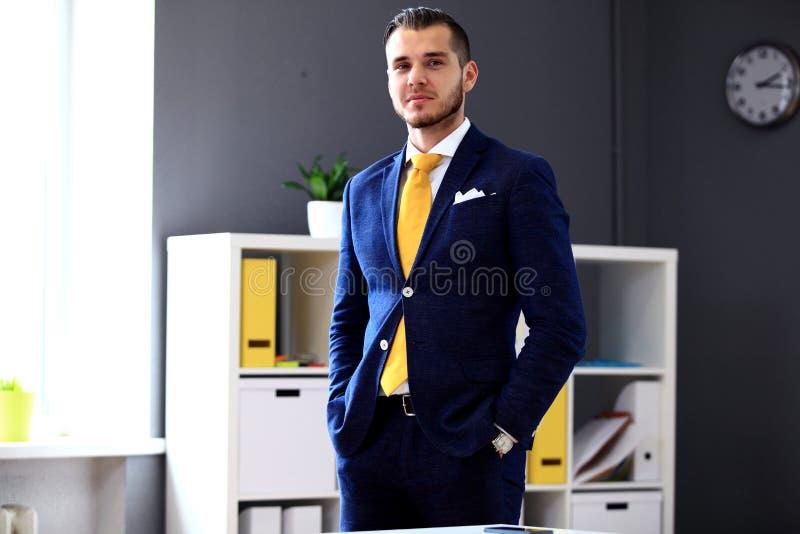 Uomo d'affari bello in vestito che esamina macchina fotografica fotografia stock