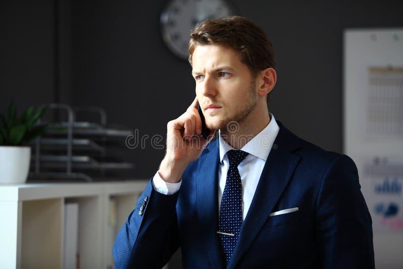 Uomo d'affari bello in vestito che parla sul telefono fotografia stock libera da diritti