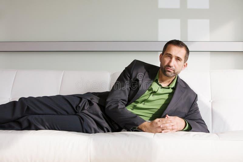 Uomo d'affari bello in vestito che si trova sullo strato e sul rilassamento fotografia stock