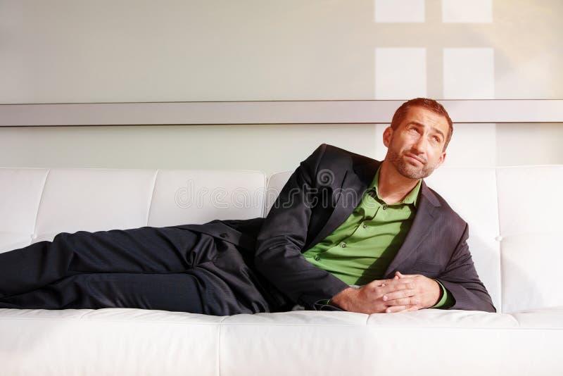 Uomo d'affari bello in vestito che si trova sullo strato e sul rilassamento immagini stock libere da diritti