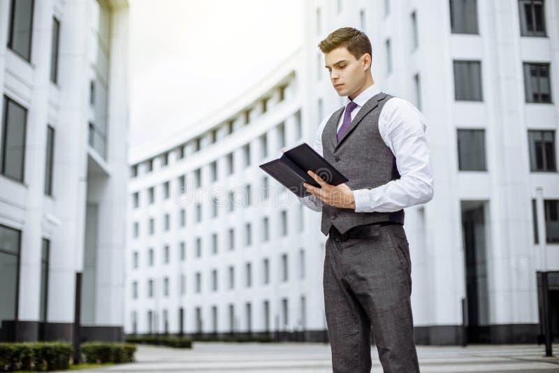 Uomo d'affari bello in vestito che sta sulla via immagine stock