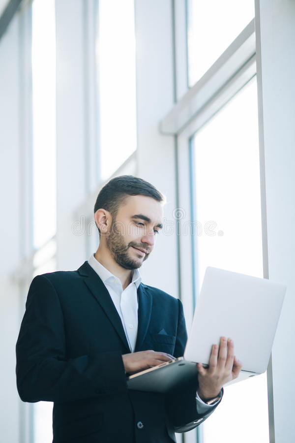 Uomo d'affari bello in vestito con il computer portatile immagine stock libera da diritti