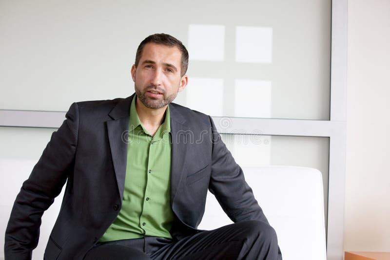 Uomo d'affari bello in vestito e camicia verde che si siedono all'interno fotografie stock libere da diritti