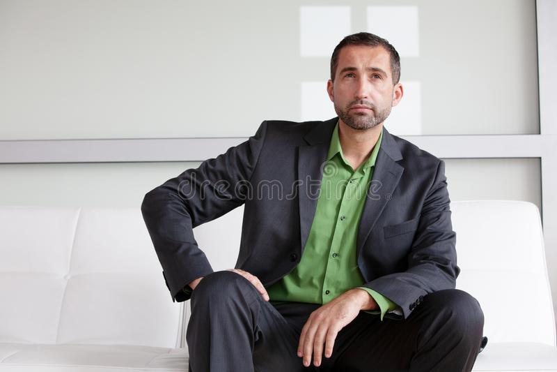 Uomo d'affari bello in vestito e camicia verde che si siedono all'interno e che sembrano pensierosi immagine stock