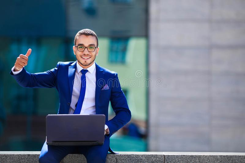 Uomo d'affari bello in vestito ed occhiali che si siedono con il computer portatile immagini stock libere da diritti