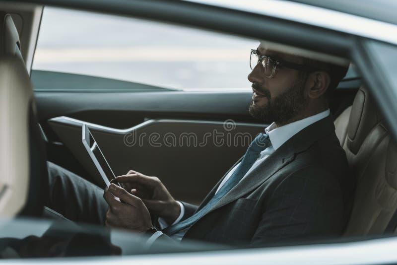 uomo d'affari bello in vetri che si siedono in automobile e che tengono compressa immagini stock