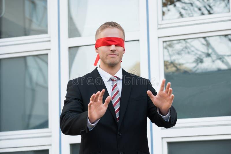 Uomo d'affari bendato Standing Against Window immagine stock