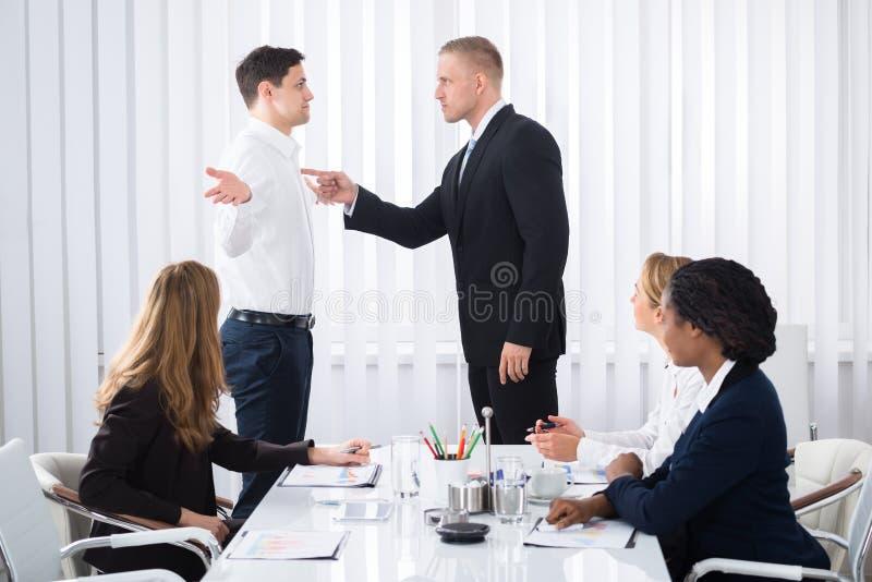 Uomo d'affari Blaming His Colleague nella riunione fotografia stock