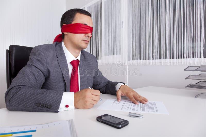 Uomo d'affari Blindfold che lavora con il suo computer portatile fotografie stock libere da diritti